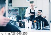 Купить «Hairdresser displaying result of work», фото № 28646256, снято 27 января 2017 г. (c) Яков Филимонов / Фотобанк Лори