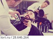 Купить «Young guy creating shape for beard of client», фото № 28646264, снято 27 января 2017 г. (c) Яков Филимонов / Фотобанк Лори