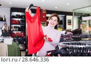Купить «Ordinary customer deciding on pretty blouse», фото № 28646336, снято 7 февраля 2017 г. (c) Яков Филимонов / Фотобанк Лори