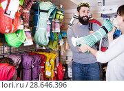 Купить «Positive man choosing alpinism equipment in store», фото № 28646396, снято 24 февраля 2017 г. (c) Яков Филимонов / Фотобанк Лори