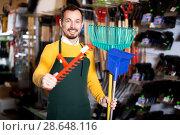 Купить «Seller displaying various items in garden equipment shop», фото № 28648116, снято 2 марта 2017 г. (c) Яков Филимонов / Фотобанк Лори