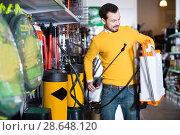 Купить «Male customer chooses a garden sprayer», фото № 28648120, снято 2 марта 2017 г. (c) Яков Филимонов / Фотобанк Лори