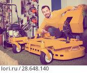 Купить «Man shows a large and powerful mulching mowers», фото № 28648140, снято 2 марта 2017 г. (c) Яков Филимонов / Фотобанк Лори