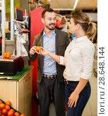 Купить «Smiling couple is weighing products», фото № 28648144, снято 4 апреля 2018 г. (c) Яков Филимонов / Фотобанк Лори