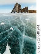 Купить «Beautiful rocky island on a background of blue sky and smooth ice with cracks. Winter Baikal lake.», фото № 28648944, снято 20 ноября 2018 г. (c) Владимир Пойлов / Фотобанк Лори
