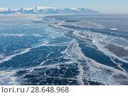 Купить «Top view of the frozen lake Baikal. Ice surface with cracks and fractures. Blue nice smooth ice with hazardous washouts», фото № 28648968, снято 26 марта 2019 г. (c) Владимир Пойлов / Фотобанк Лори
