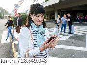 Симпатичная женщина средних лет набирает номер на телефоне. Стоковое фото, фотограф Игорь Низов / Фотобанк Лори
