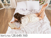 Купить «Long-hair lass wearing wraparound reading a book», фото № 28649160, снято 1 апреля 2018 г. (c) Сергей Дубров / Фотобанк Лори