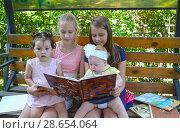 Купить «Девочки-школьницы с маленькими сестренками рассматривают книгу на скамейке в парке», фото № 28654064, снято 28 июня 2018 г. (c) Ирина Борсученко / Фотобанк Лори