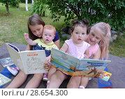 Купить «Девочки с маленькими сестричками  читают книжки, сидя на траве в саду», фото № 28654300, снято 28 июня 2018 г. (c) Ирина Борсученко / Фотобанк Лори