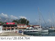 Современные красивые яхты пришвартованы в порту Кемер, на фоне ресторана быстрого питания Макдоналдс (2018 год). Редакционное фото, фотограф Светлана Шимкович / Фотобанк Лори