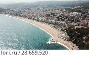 Купить «Picturesque aerial view of Mediterranean coastal town of Lloret de Mar in Catalonia, Spain», видеоролик № 28659520, снято 11 июня 2018 г. (c) Яков Филимонов / Фотобанк Лори
