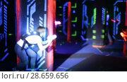 Modern young people playing laser tag on dark labyrinth in bright beams of laser pistols. Стоковое видео, видеограф Яков Филимонов / Фотобанк Лори