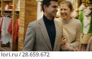Купить «Couple is satisfied shopping and walking with package in the clothes store.», видеоролик № 28659672, снято 27 марта 2018 г. (c) Яков Филимонов / Фотобанк Лори