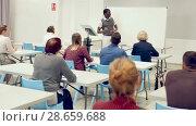 Купить «Smiling African American teacher giving presentation for students in lecture hall», видеоролик № 28659688, снято 23 мая 2018 г. (c) Яков Филимонов / Фотобанк Лори