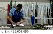 Купить «Male master is working on his workplace in the window workshop.», видеоролик № 28659696, снято 23 мая 2018 г. (c) Яков Филимонов / Фотобанк Лори