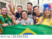 Купить «На Никольской улице в Москве группа футбольных фанатов из разных стран, крича и жестикулируя, фотографируется с национальным флагом Бразилии. Чемпионат мира по футболу FIFA 2018, Россия», фото № 28659832, снято 24 июня 2018 г. (c) Наталья Николаева / Фотобанк Лори