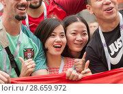 Купить «Две кричащие девушки-болельщицы на Никольской улице в Москве фотографируются с национальным флагом. Чемпионат мира по футболу FIFA 2018, Россия», фото № 28659972, снято 24 июня 2018 г. (c) Наталья Николаева / Фотобанк Лори