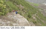 Купить «Couple walking along the stairs on the trek around Manaslu, village Prok, Nepal», видеоролик № 28660356, снято 17 июня 2018 г. (c) Dzmitry Astapkovich / Фотобанк Лори