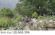 Купить «Tourists walking in nepalese village Prok, trek around mountain Manaslu, Nepal», видеоролик № 28660396, снято 17 июня 2018 г. (c) Dzmitry Astapkovich / Фотобанк Лори