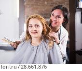 Купить «Mature hairdresser is doing fashionable haircut to young woman with scissors and comb», фото № 28661876, снято 7 марта 2017 г. (c) Яков Филимонов / Фотобанк Лори