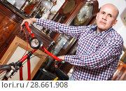 Купить «Elderly man carefully examining antiques», фото № 28661908, снято 15 мая 2018 г. (c) Яков Филимонов / Фотобанк Лори