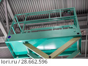 Купить «Hydraulic scissor lift platform. The platform of the lift is raised under the roof of the building», фото № 28662596, снято 20 сентября 2017 г. (c) Андрей Радченко / Фотобанк Лори