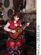 Красивая цыганка возле камина играет на гитаре. Стоковое фото, фотограф Марина Володько / Фотобанк Лори