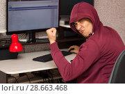 Купить «Интернет тролль у компьютера. Агрессивный молодой человек пишет вредные комментарии в сети и радуется», фото № 28663468, снято 8 мая 2018 г. (c) Лариса Капусткина / Фотобанк Лори