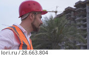 Купить «Man in a helmet, architect, engineer, manager tells about the progress of construction in evening stock footage video», видеоролик № 28663804, снято 23 июня 2018 г. (c) Юлия Машкова / Фотобанк Лори