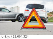 Купить «Accident or crash with two automobile. Road warning triangle sign in focus», фото № 28664324, снято 22 сентября 2013 г. (c) Дмитрий Калиновский / Фотобанк Лори
