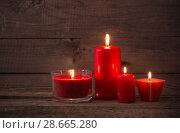 Купить «red candles on dark wooden background», фото № 28665280, снято 14 ноября 2017 г. (c) Майя Крученкова / Фотобанк Лори
