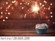 Купить «cupcake with sparkler on old wooden background», фото № 28665288, снято 14 декабря 2017 г. (c) Майя Крученкова / Фотобанк Лори