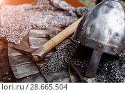 Купить «Iron helmet in armor and ax», фото № 28665504, снято 30 июня 2018 г. (c) Дмитрий Бачтуб / Фотобанк Лори