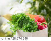 Купить «close up of paper bag with vegetable food», фото № 28674340, снято 3 июня 2016 г. (c) Syda Productions / Фотобанк Лори