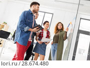 Купить «creative team looking at glass board at office», фото № 28674480, снято 1 апреля 2018 г. (c) Syda Productions / Фотобанк Лори