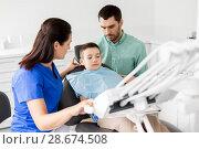 Купить «father and son visiting dentist at dental clinic», фото № 28674508, снято 22 апреля 2018 г. (c) Syda Productions / Фотобанк Лори