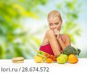 Купить «doubting woman with fruits looking at hamburger», фото № 28674572, снято 23 марта 2013 г. (c) Syda Productions / Фотобанк Лори