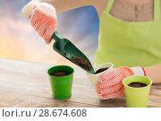 Купить «close up of woman hands with trowel adding soil», фото № 28674608, снято 3 марта 2015 г. (c) Syda Productions / Фотобанк Лори