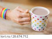 Купить «hand with cup of cacao and gay awareness wristband», фото № 28674712, снято 14 ноября 2017 г. (c) Syda Productions / Фотобанк Лори