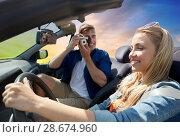 Купить «man photographing woman driving car by film camera», фото № 28674960, снято 28 мая 2016 г. (c) Syda Productions / Фотобанк Лори