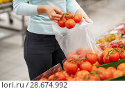 Купить «woman with bag buying tomatoes at grocery store», фото № 28674992, снято 2 ноября 2016 г. (c) Syda Productions / Фотобанк Лори