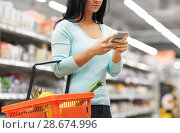 Купить «woman with smartphone buying food at supermarket», фото № 28674996, снято 2 ноября 2016 г. (c) Syda Productions / Фотобанк Лори