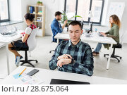 Купить «creative man with smartwatch working at office», фото № 28675064, снято 1 апреля 2018 г. (c) Syda Productions / Фотобанк Лори