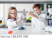 Купить «kids with flask and magnifier at chemistry class», фото № 28675100, снято 19 мая 2018 г. (c) Syda Productions / Фотобанк Лори