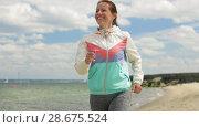 Купить «smiling woman running along beach», видеоролик № 28675524, снято 25 июня 2018 г. (c) Syda Productions / Фотобанк Лори