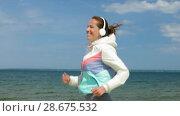 Купить «smiling woman with headphones running along beach», видеоролик № 28675532, снято 25 июня 2018 г. (c) Syda Productions / Фотобанк Лори