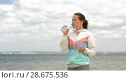 Купить «woman drinking water after exercising on beach», видеоролик № 28675536, снято 25 июня 2018 г. (c) Syda Productions / Фотобанк Лори