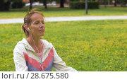 Купить «woman with earphones meditating at park», видеоролик № 28675580, снято 25 июня 2018 г. (c) Syda Productions / Фотобанк Лори