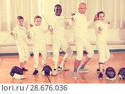 Купить «Group portrait of young fencers with coaches holding rapiers in training room», фото № 28676036, снято 30 мая 2018 г. (c) Яков Филимонов / Фотобанк Лори